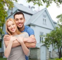 Happy Couple in Front Home a Home They Just Purchased Home Insurance For
