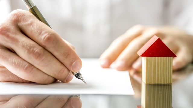 Conceptual image of a man signing a FHA loan Contract
