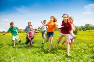 Happy Group pf kids running in a green field